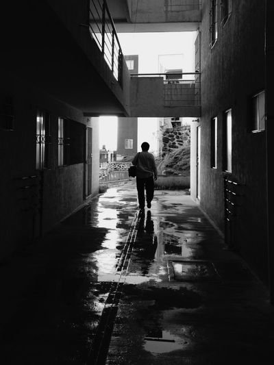 Rear view of man walking on alley amidst buildings in city