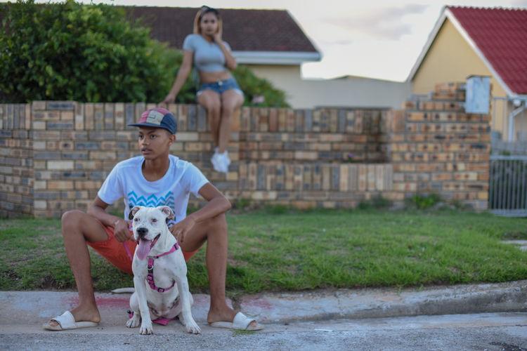 Full length of dog sitting against building