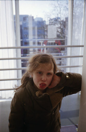 Portrait Of Girl Making Face While Standing By Window