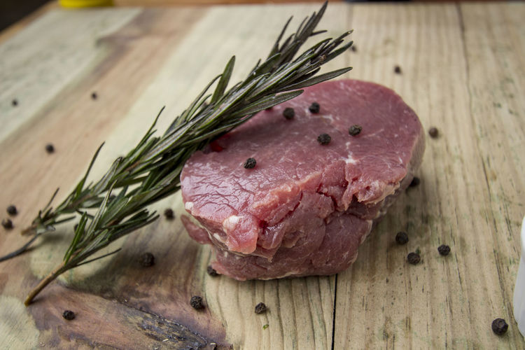Close-Up Of Meat With Black Peppercorn And Rosemary Leaves On Table