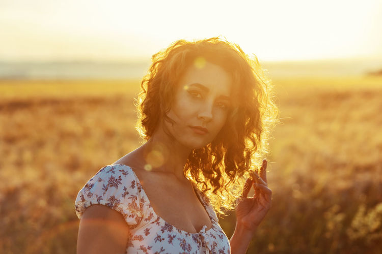 Portrait of beautiful woman standing on land against sky during sunset