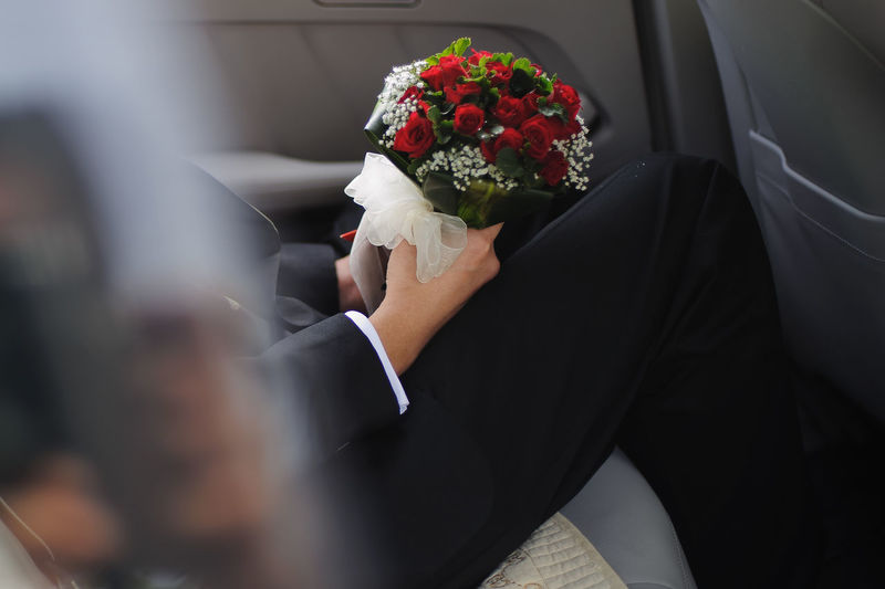 Midsection of groom with bouquet sitting in car