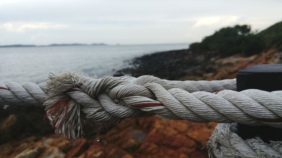 Close-up of rope tied up at beach against cloudy sky