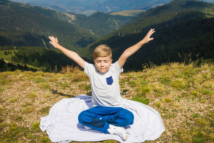 Little boy with arms outstretched sitting in lotus position and enjoying in freedom in nature.
