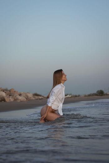 Beautiful woman sitting at beach against sky