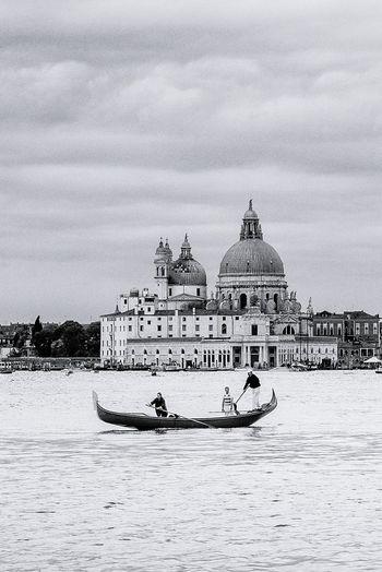 People rowing gondola in canal against santa maria della salute
