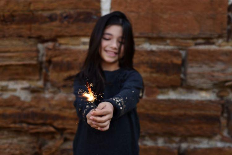 Cute girl holding lit sparkler against brick wall