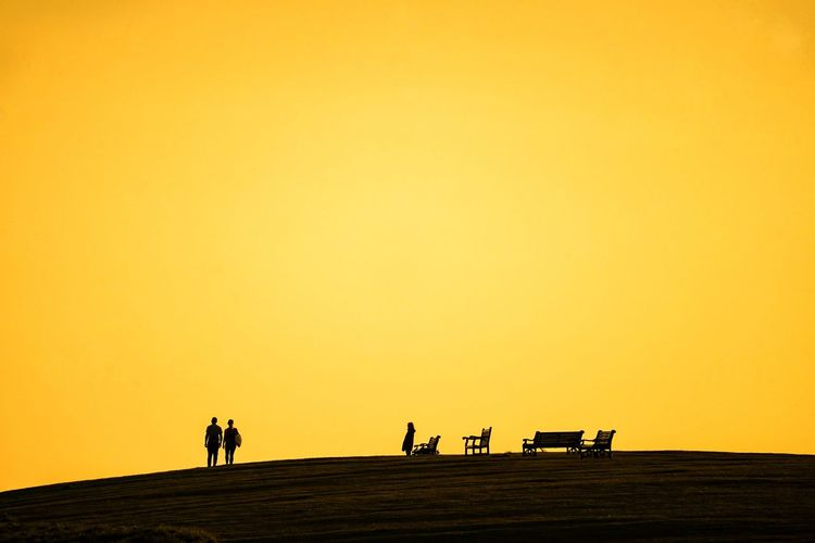 Silhouette people walking on road against orange sky