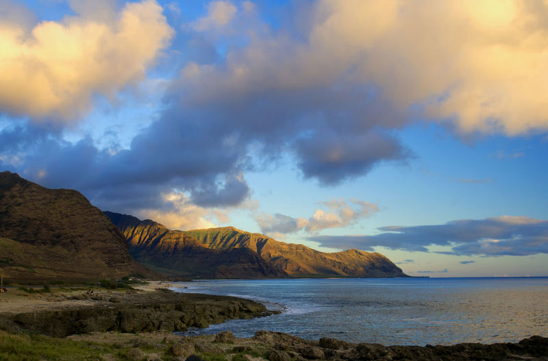 Scenic View Of Sea By Mountains Against Cloudy Sky At Hawaii Islands