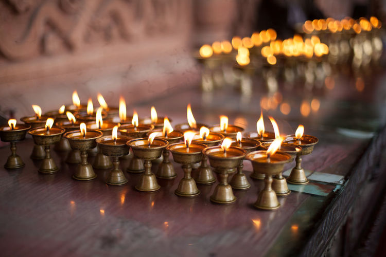 Oil lamps burning on counter at temple