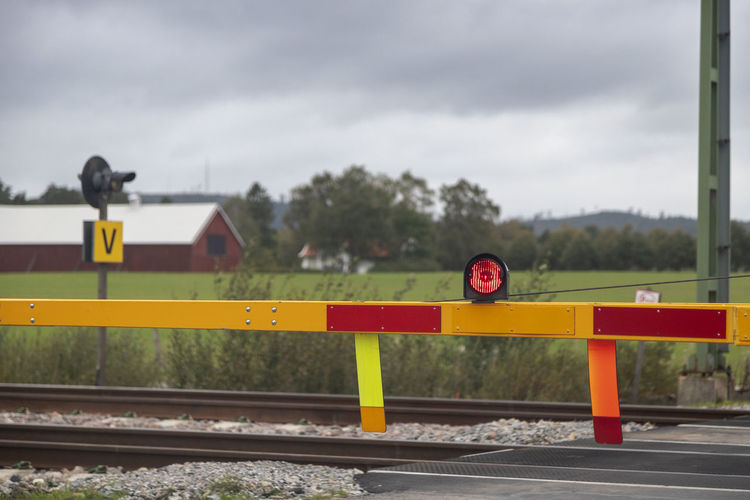 Rail road sign by railroad tracks against sky Transportation Railroad Track Traffic Outdoors Train Road Yellow Equipment Sign Sky Nature Communication No People Cloud - Sky Day Rail Transportation Focus On Foreground Tree Safety Track Warning Sign Road Sign Protection