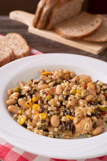 Spelled, chickpea, tuna and corn salad arranged on rustic table with bread Bean Bowl Bread Breakfast Chick-pea Close-up Crockery Food Food And Drink Freshness Healthy Eating High Angle View Indoors  Meal No People Plate Ready-to-eat Serving Size Still Life Table Vegetable Vegetarian Food Wellbeing