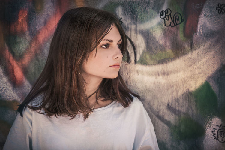Portrait of beautiful young woman against graffiti wall