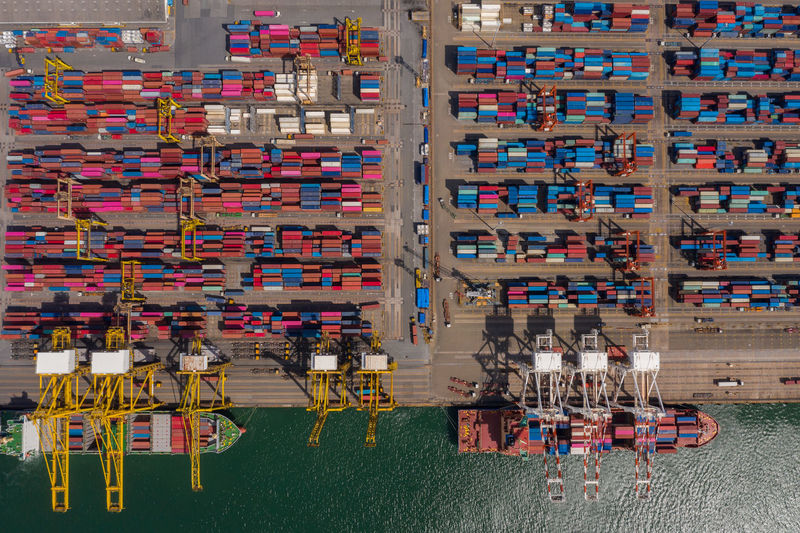 Container ship loading and unloading in sea port, aerial view of business logistic import and export