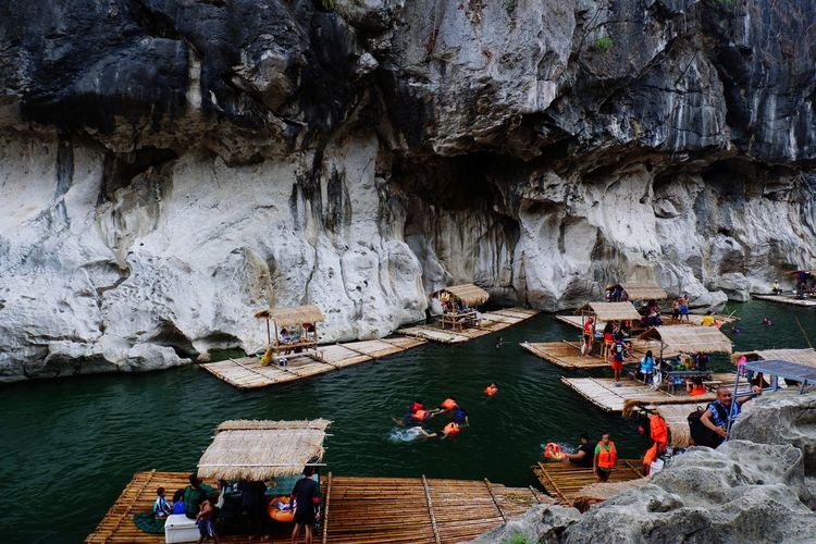 People on wooden rafts in lake against rock formation