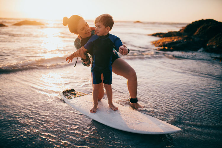 Mother teaching son to surf on beach during sunset