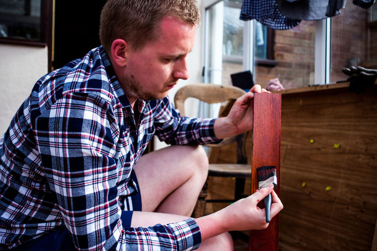 Side view of young man painting wooden plank while crouching at home