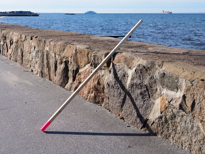 Water Sea Nature No People Day Tranquility Horizon Over Water Tranquil Scene Beach Scenics - Nature Horizon Land Rock Beauty In Nature Sunlight Outdoors Sky Rock - Object Transportation Triangle Stick Latch Leaning Shadows Pythagoras Mathematics Geometry Pink Pink Color