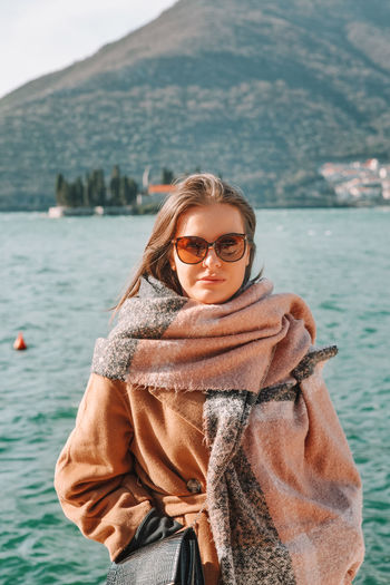 Young woman wearing sunglasses standing against mountain