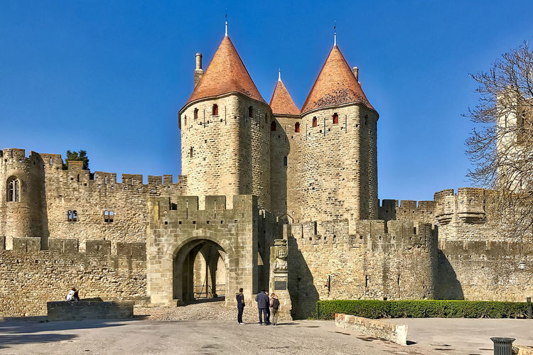 The main entrance to the medieval city of Carcassonne in France. Architecture Blue Sky Building Exterior Built Structure Carcassonne City Wall Clear Sky Day France Gate History Main Entrance Medieval Outdoors Red Roofs Towers Travel Destinations