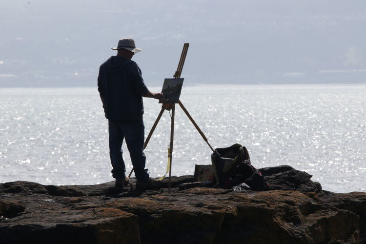 Rear view of mature man painting while standing on rock by sea against sky during sunny day