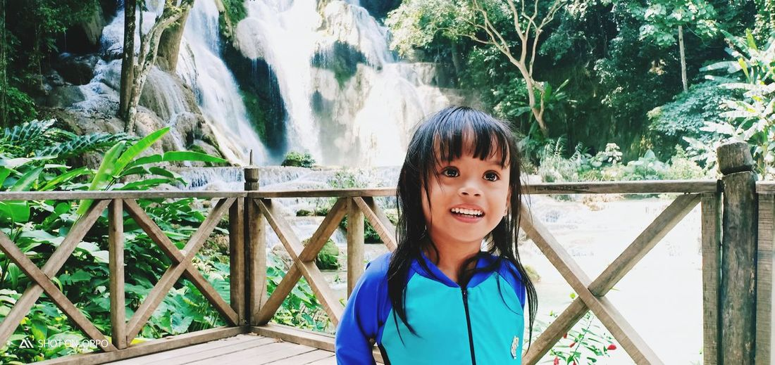 Smiling girl standing by railing against waterfall