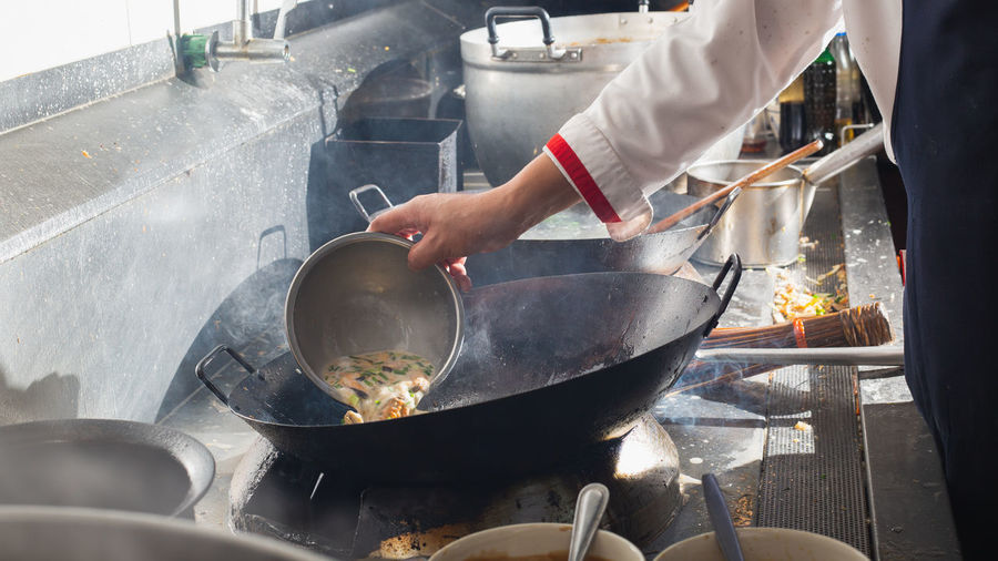 Chef stir fry in wok. professional cooking in kitchen