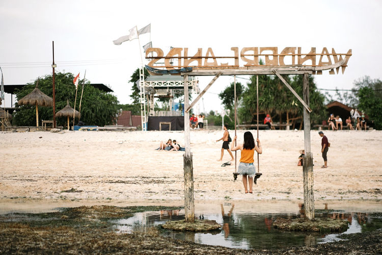 Adult Architecture Built Structure Day Gili Trawangan Group Of People Incidental People Leisure Activity Lifestyles Men Nature Outdoors People Real People Reflection Sky Swing Tree Water Waterfront Women