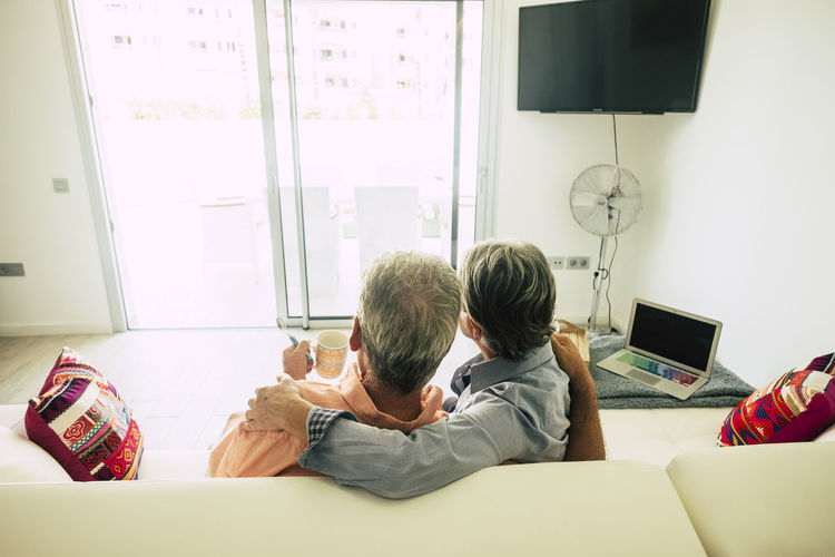 Rear view of senior couple sitting on sofa at home