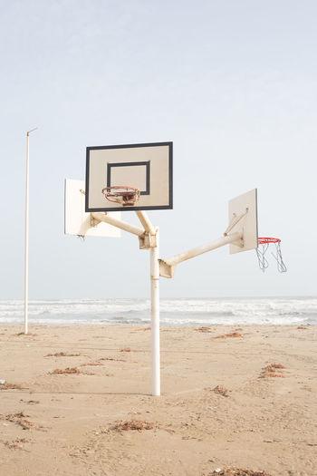 Basketball hoop on beach against clear sky