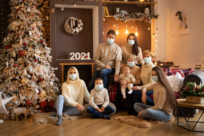 Portrait of cheerful family weraing mask sitting at home by christmas tree