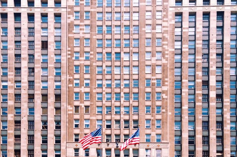 Close-up of American flag against buildings