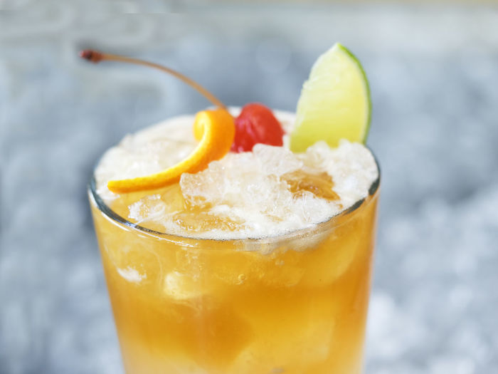 Close-up of lemonade garnish with fruits in glass on crushed ice