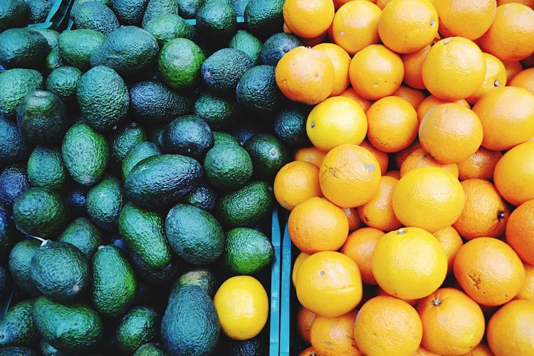 Full frame shot of oranges with avocadoes for sale at market stall