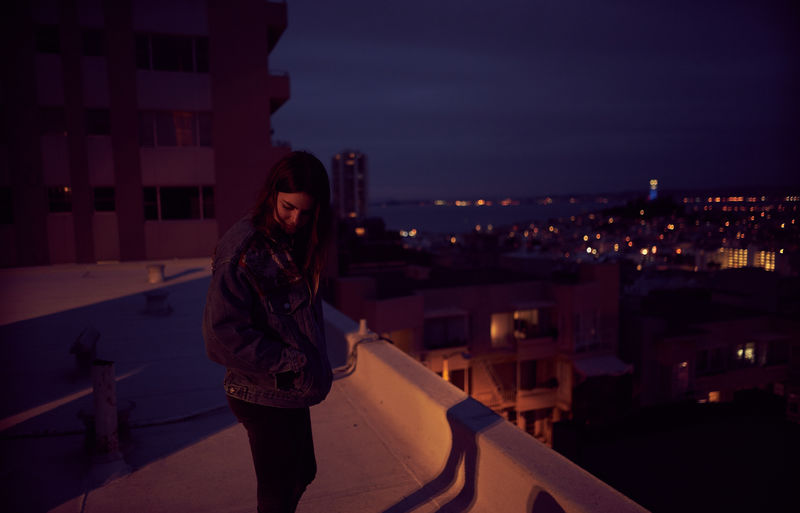 Young woman standing on illuminated city against sky at night