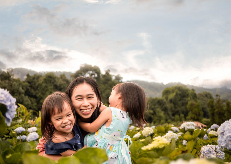Portrait of smiling mother with cute daughters against sky