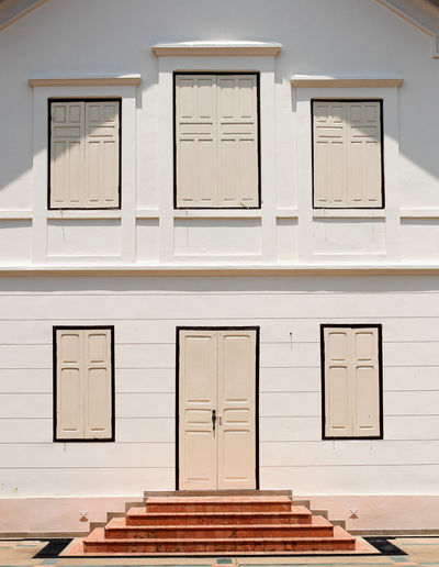 Doors and windows on the white wall. Building Exterior No People Building White Color Sunlight Outdoors City Door Window Wood - Material Symmetry Edifice