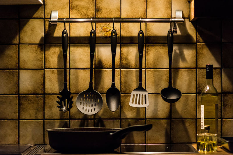 Cooking utensils hanging on wall at home