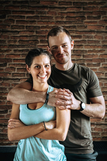 Portrait of smiling couple standing against brick wall
