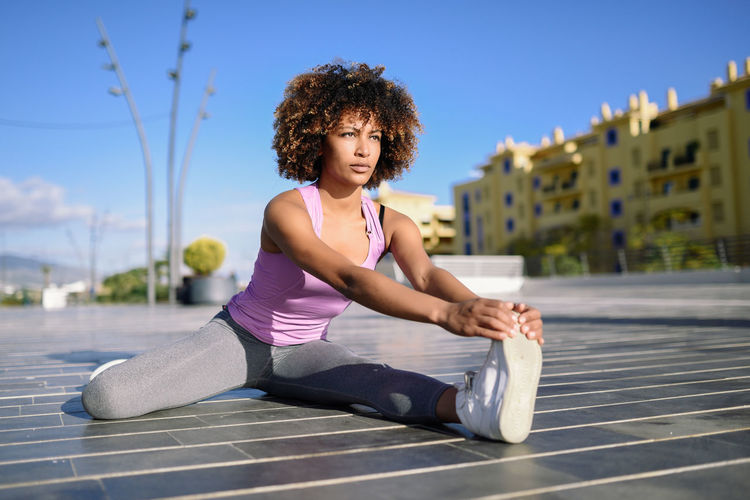 Woman exercising while sitting on footpath
