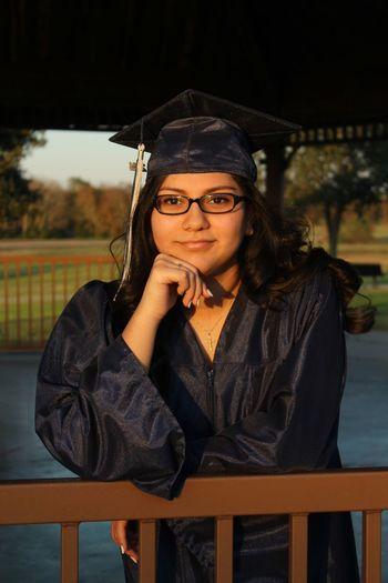 Portrait of young woman in graduation gown leaning on railing