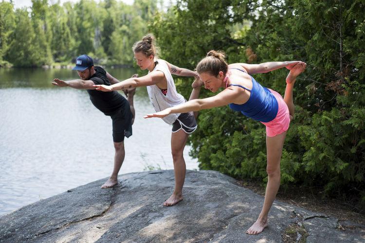 Friends enjoying on lake against trees