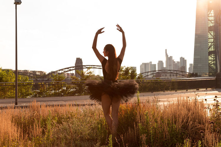 Rear View Of Female Ballet Dancer Dancing On Grassy Field In City Against Clear Sky