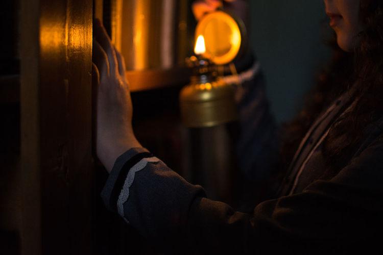 Close-up of hand holding illuminated electric lamp