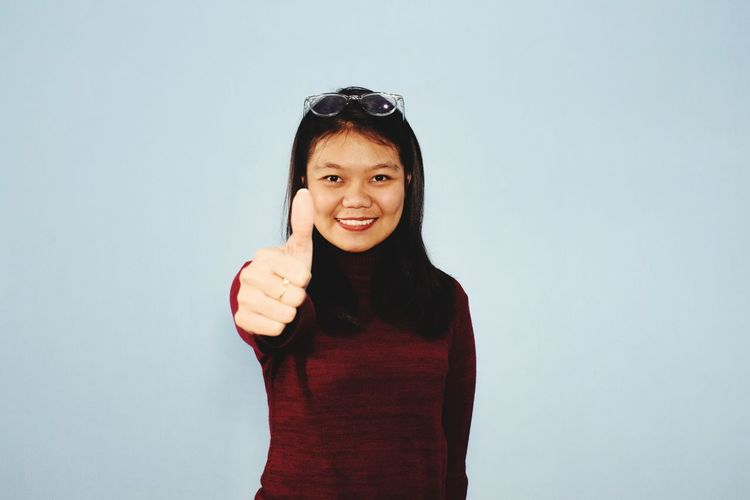 Portrait of smiling young woman against white background