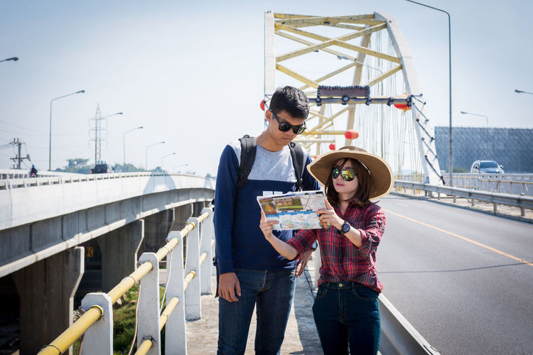 Couple reading map while standing on bridge in city