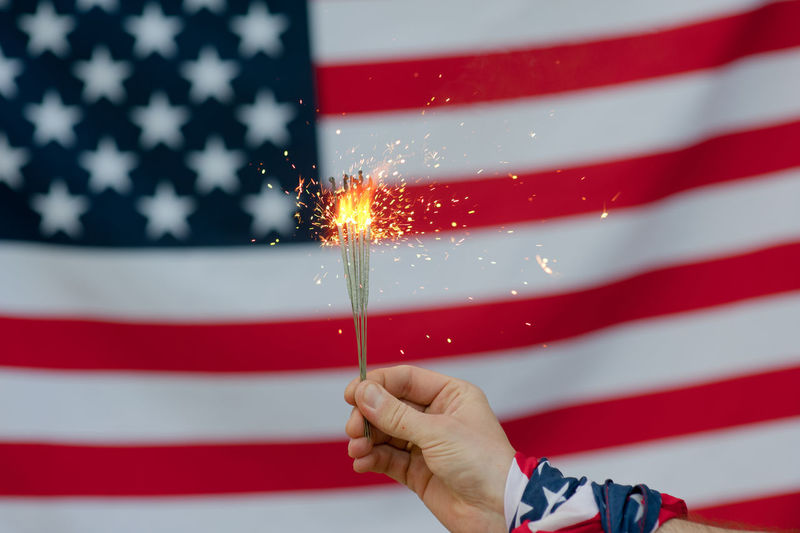 USA flag Red Flag Celebration Patriotism Striped Human Hand Hand Holding One Person Motion Star Shape Burning Event Shape Pride Sparkler Firework Freedom Finger Firework - Man Made Object Firework Display Sparks