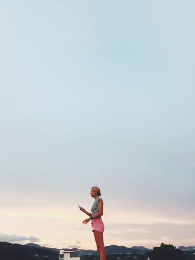 Side View Of Woman Standing Against Cloudy Sky During Sunset