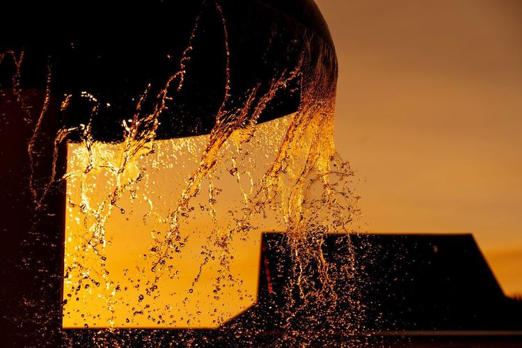 Close-up of water splashing in illuminated fountain against sky during sunset