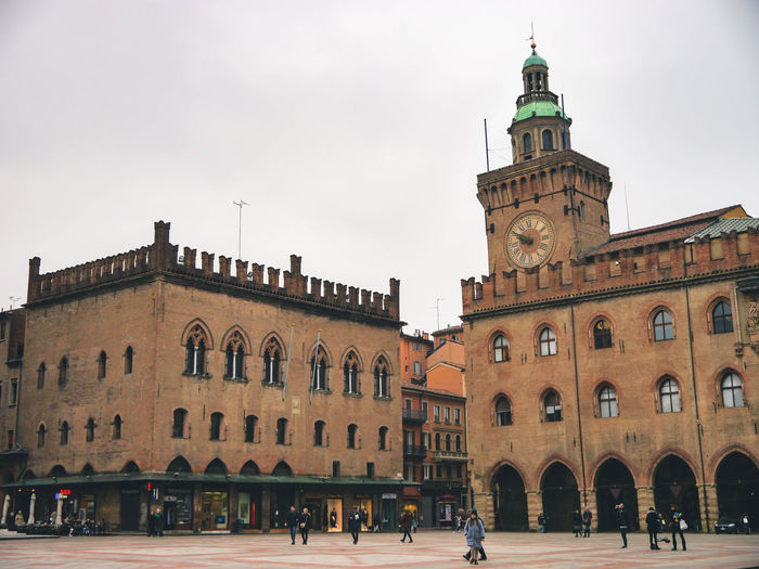 Piazza Maggiore Adult Architecture Building Exterior Built Structure City Clock Clock Tower Day History Large Group Of People Men Outdoors People Real People Sky Travel Destinations